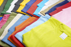 Multicolored t-shirts. Collection of casual T-shirts in different colors filling the frame stock photos