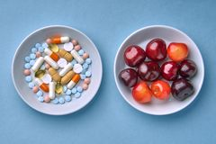 Multicolored tablets and pills, fruits and berries stock images