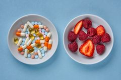 Multicolored tablets and pills, fruits and berries royalty free stock images