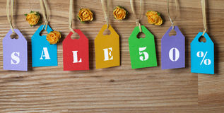 Multicolored tags lettering sale 50% with paper flowers on wood. Stock Images