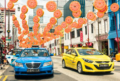 Multicolored taxi cabs driving on South Bridge Road in Singapore Stock Image