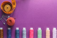 Multicolored Threads on a purple background with tailor tape measure.  royalty free stock photo