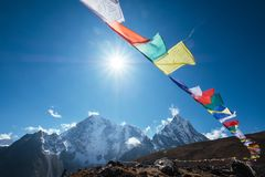 Free Multicolored Tibetan Prayer Flags With Mantras Flapping On The Wind With High Himalayas Range Background. Taboche 6495m And Royalty Free Stock Photo - 163551995