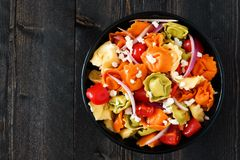 Multicolored tortellini pasta salad, overhead view on dark wood Stock Images
