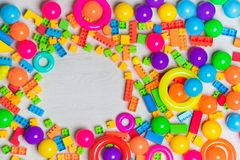 Multicolored toys blocks and bricks. Close up top view shot of multicolored toys, blocks, rings, interlocked lego, letters, wooden bricks, building game pieces stock photo