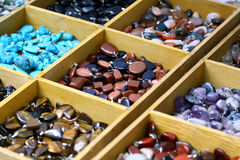 Multicolored trinket stones. On sale in different boxes Royalty Free Stock Photo