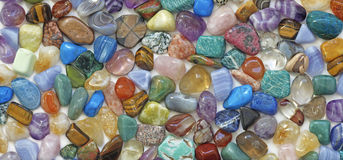 Multicolored tumbled crystal stones background. A large quantity of different colored healing tumbled gem stones making up a backdrop for use as a background Royalty Free Stock Images