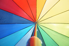 Multicolored umbrella against the sunny sky Royalty Free Stock Images