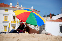 Multicolored umbrella on  beach Royalty Free Stock Images