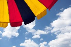 Multicolored umbrella detail in front of blue sky stock images