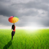 Multicolored umbrella woman jumping in green rice field and rainclouds Stock Photo