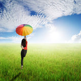 Multicolored umbrella woman jumping in green rice field and sun sky Royalty Free Stock Photos
