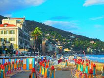 Multicolored umbrellas on the beach in Alassio, province of Savona, Sanremo region, Italy. City at sunset stock images