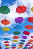 Multicolored umbrellas hanging high above the ground Stock Image