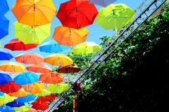 Multicolored umbrellas hanging over head on the street against the blue sky and tree branches Stock Photos