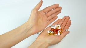 Multicolored vitaminen en tabletten in de handen van het meisje Apotheek, het gezonde eten Giet van hand aan hand stock videobeelden