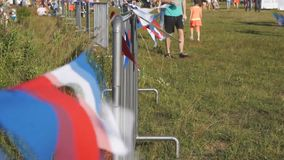Multicolored vlaggen op de omheining die langzaam de omheining van de winddraad op het picknickgebied bewegen