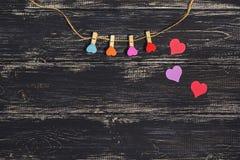 Multicolored wasknijpers van een hart op een koord op een donkere houten achtergrond De dag van de valentijnskaart `s Stock Foto's