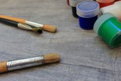 Multicolored watercolor paints with several paintbrushes on grey stone textured background. Royalty Free Stock Photography