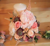 Multicolored wedding roses and tulips bouquet with candle Stock Photos