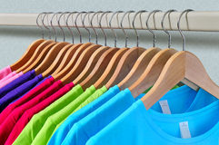 Multicolored women's t-shirts hang on wooden hangers. Royalty Free Stock Images