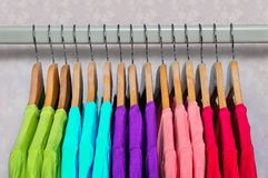 Multicolored women`s t-shirts hanging on wooden hangers. Stock Image