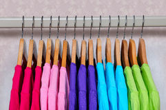 Multicolored women's t-shirts hanging on wooden hangers. Royalty Free Stock Photos