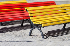 Multicolored wooden benches. sunny day park interior Stock Photography