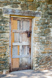 Multicolored Wooden Door against Worn Stone Wall Royalty Free Stock Photo