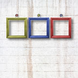 Multicolored  wooden frames for pictures on stone wall Stock Photo