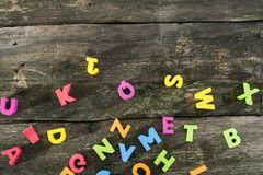 Multicolored wooden letters on vintage board Royalty Free Stock Photos