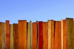 Wooden fence and blue sky. Multicolored wooden wall and blue sky. A colored wall of wood with a lot of copy space. Wooden fence and blue sky. Colored Painted stock photo