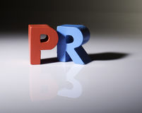 Multicolored word PR made of wood. Stock Images