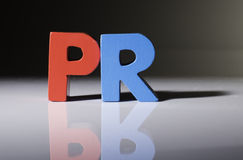 Multicolored word PR made of wood. Stock Photos