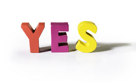 Multicolored word yes made of wood. Royalty Free Stock Photos