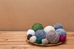 Multicolored yarn  balls in a straw basket on a wooden table Royalty Free Stock Images