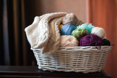 Multicolored yarn in a white wicker basket. Knitted socks Stock Photography
