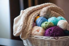 Multicolored yarn in a white wicker basket. Knitted socks Royalty Free Stock Image