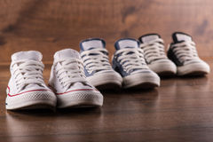 Multicolored youth gym shoes on floor Royalty Free Stock Photos