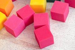 Multicolored zachte schuimkubussen bij kinderenspeelplaats Helder kleurrijk speelgoed Het vermaak en de decoratie van de jonge ge stock afbeelding