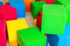 Multicolored zachte schuimkubussen bij kinderenspeelplaats Helder kleurrijk speelgoed Het vermaak en de decoratie van de jonge ge stock afbeeldingen