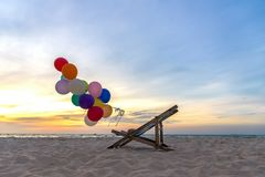 Multicolour balloons with canvas bed for relax on sunset tropical beach sunny day. Stock Images