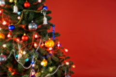 Multicolour Christmas tree with decorations and lights, red background Royalty Free Stock Photography