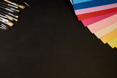 Multicolour papper och borstar med kopieringsutrymme på svart Royaltyfria Bilder