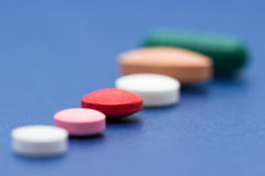 Multicolour pills. Various multiple coloured and shaped medicine pills, on blue background royalty free stock photography
