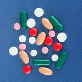 Multicolour pills. Various multiple coloured and shaped medicine pills, on blue background stock image