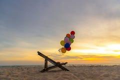 Multicoloured ballons met canvasbed voor ontspannen op zonnige dag van het zonsondergang de tropische strand Royalty-vrije Stock Foto's