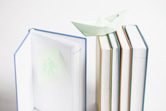 Multicoloured Books with Paper Boat. Multicoloured books with blue paper boat and post-it note Stock Images