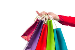 Multicoloured and bright shopping packages hanging on female red Stock Photo