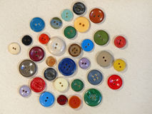 Multicoloured buttons on beige fabric. Royalty Free Stock Image